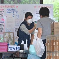 検温をして避難所に入る被災者。掲示板には台風対策についてのお知らせも張り出されていた=熊本県多良木町で2020年9月5日午後5時7分、徳野仁子撮影