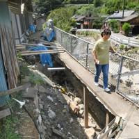 陥没した自宅の庭の脇を通って外にでる高沢千代子さん。前には球磨川支流の中園川が流れる=熊本県球磨村神瀬で2020年9月4日午後0時15分、矢頭智剛撮影