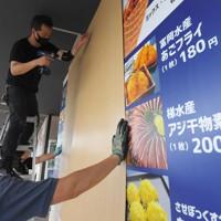 道の駅のメニュー看板に板を打ち付ける従業員ら=長崎県佐世保市で2020年9月6日午後2時5分、津村豊和撮影
