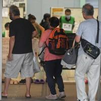 台風10号が接近する中、多くの荷物を手に避難所に入る人たち=熊本県人吉市で2020年9月6日午後4時15分、矢頭智剛撮影