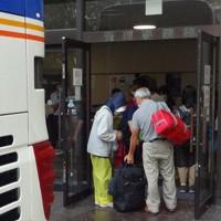 バスから降り熊本県立劇場に入る熊本県人吉市からの避難者=熊本市中央区で2020年9月6日午後0時36分、山田宏太郎撮影