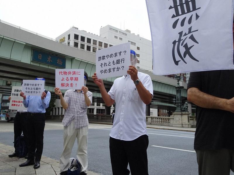 「日本橋」の看板を背に、スルガ銀行に抗議する購入者=東京都中央区で9月2日午前8時、今沢真撮影