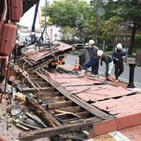 強風で倒れた看板を撤去する作業員