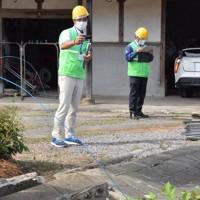 発生した突風で倒れたブロック塀を調べる大分地方気象台の職員たち