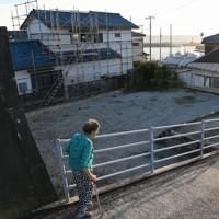台風15号の被害からまもなく1年。被害を受けた住宅(左奧)の修理がようやく終わったと話す女性。台風が千葉に上陸した夜は家に一人で、雨風がひどく、夜中に停電して本当に恐かったという。周囲には台風後に取り壊して更地になった場所も多く、「寂しくなっていくね」と話した=千葉県館山市布良で2020年9月4日午後5時27分、竹内紀臣撮影