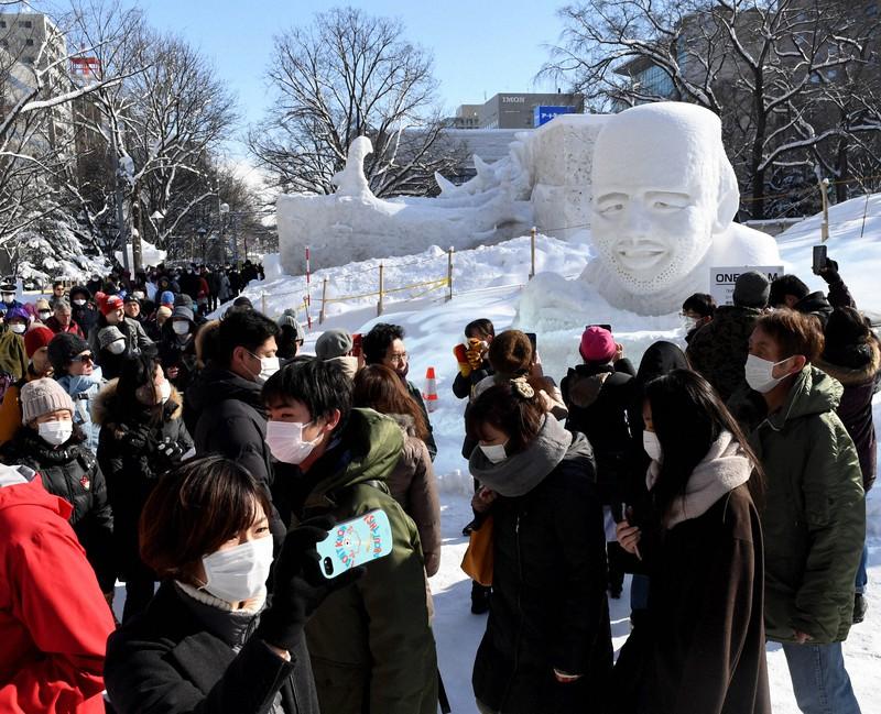 ラグビー日本代表のリーチ・マイケル選手の雪像(右奥)も登場し、マスク姿の観光客でにぎわった「さっぽろ雪まつり」=札幌市中央区で2020年2月4日、竹内幹撮影