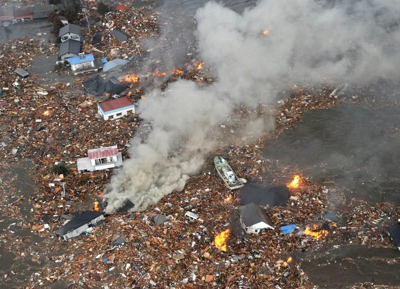 仙台空港周辺で大津波にのみ込まれる多くの家屋。火災も発生している=2011年3月11日午後4時ごろ、本社ヘリから手塚耕一郎撮影