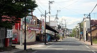 One of the town of Futaba's main streets is seen with dilapidated shops and devoid of people or cars, in Fukushima Prefecture on Aug. 12, 2020. (Mainichi/Tomonari Takao)