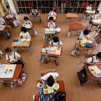 前を向いて黙々と給食を食べる児童たち。コロナ禍の前は班になってまとまって食事を取っていた=大阪市浪速区で2020年7月20日、山田尚弘撮影