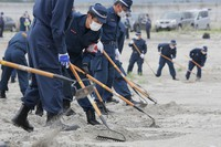 Police officers are seen searching for clues that could lead to information on people who went missing after the tsunami caused by the Great East Japan Earthquake on March 11, 2011, in the city of Minamisoma, Fukushima Prefecture, on Sept. 11, 2020, nine and a half years to the day since the disaster. (Mainichi/Daisuke Wada)