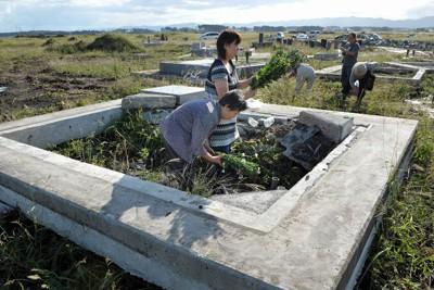 震災による津波で基礎だけ残して墓石が流された墓地で花を手向ける女性ら。福島県南相馬市原町区下渋佐では68世帯260人あまりの集落が津波に直撃され全壊。住民ら三十数人が亡くなった。海岸から200メートルほどの墓地も墓石の多くが流失した=福島県南相馬市で2011年9月23日午後、小林努撮影