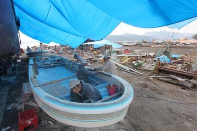 雨が降る中、ブルーシートの下で漁船の改修をする作業員ら=岩手県大槌町安渡で2011年9月30日午前10時45分、長谷川直亮撮影