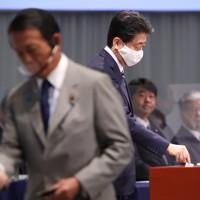 自民党総裁選で投票する安倍晋三首相(右)。左は麻生太郎副首相=東京都内のホテルで2020年9月14日午後2時7分、宮武祐希撮影