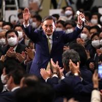 自民党の新総裁に決まり、議員たちの拍手に両手を上げて応える菅義偉官房長官=東京都内のホテルで2020年9月14日午後3時21分、宮武祐希撮影