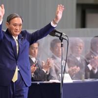 自民党総裁選終了後、壇上で議員らに手を振る菅義偉官房長官=東京都内のホテルで2020年9月14日午後3時37分、宮武祐希撮影