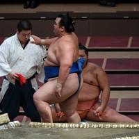 明生に寄り切りで敗れ、肩を借りて土俵を後にする琴奨菊(右)=東京・両国国技館で2020年9月14日、北山夏帆撮影
