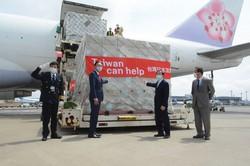 貨物機から降ろされたマスクの入った荷物の前に立つ台北駐日経済文化代表処の謝長廷代表(左から3人目)ら=成田空港で2020年4月21日、中村宰和撮影