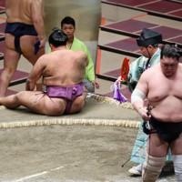 照ノ富士(右)に上手投げで敗れ、座り込む朝乃山=東京・両国国技館で2020年9月15日、吉田航太撮影