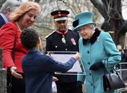 慈善団体を訪問中、子どもから絵を披露されるエリザベス女王=ロンドンで2018年12月5日、AP