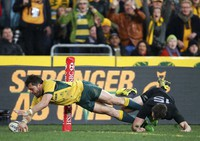 In this Aug. 8, 2015, file photo, Australia's Adam Ashley-Cooper, left, dives past New Zealand's Ben Smith to score a try during their Rugby Championship match in Sydney. (AP Photo/Rick Rycroft)