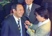 Yoshihide Suga has an assembly member's badge pinned to his suit as he attends the Diet for the first time for a special session on Nov. 7, 1996, after being elected for the first time in the 1996 October House of Representatives election. (Mainichi)