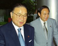 Yoshihide Suga, right, departs from a commercial TV station with Seiroku Kajiyama, who was running for the president of the Liberal Democratic Party, in Tokyo on July 19, 1998. (Mainichi)