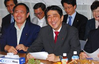 Yoshihide Suga, left, smiles with Chief Cabinet Secretary Shinzo Abe, who visited a national assembly members' group supporting the
