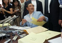 Minister of Internal Affairs and Communications Yoshihide Suga explains about a scandal related to his office's expenses while showing receipts to the media in Tokyo on Aug. 25, 2007. (Mainichi/Masahiro Kawata)