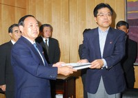 Former Minister of Internal Affairs and Communications Yoshihide Suga hands over documents to his successor, Hiroya Masuda, at the ministry in Tokyo's Chiyoda Ward on Aug. 28, 2007. (Mainichi/Emi Naito)