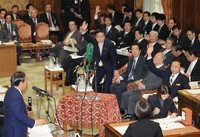 Yoshihide Suga, left, then a member of the opposition Liberal Democratic Party, questions Prime Minister Yukio Hatoyama, from the Democratic Party, at a House of Representatives budget committee session in the Diet building on Nov. 4, 2009. (Mainichi/Akihiro Hirata)