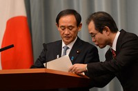 Chief Cabinet Secretary Yoshihide Suga, left, is seen discussing a hostage situation involving Japanese citizens in Algeria, in a press conference at the prime minister's office on Jan. 18, 2013. (Mainichi/Hiroshi Maruyama)