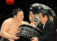 Then Chief Cabinet Secretary Yoshihide Suga, right, gives the Prime Minister's trophy to tournament-winner Yokozuna Hakuho, at the Ryogoku Kokugikan sumo venue in Tokyo on Jan. 26, 2014. (Mainichi/Kan Takeuchi)