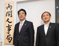 Then Chief Cabinet Secretary Yoshihide Suga, right, and then Prime Minister Shinzo Abe are seen after setting the sign for the newly established Cabinet Bureau of Personnel Affairs in Tokyo's Chiyoda Ward on May 30, 2014. (Pool photo)