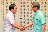 Then Chief Cabinet Secretary Yoshihide Suga, left, and then Okinawa Gov. Takeshi Onaga shake hands before their meeting at the Okinawa prefectural government office in Naha, on Aug. 12, 2015. (Mainichi)