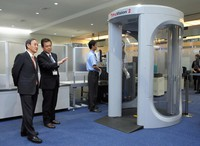 Then Chief Cabinet Secretary Yoshihide Suga, left, receives explanations about body scanners at Haneda Airport in Tokyo's Ota Ward on Dec. 2, 2015. (Pool photo)