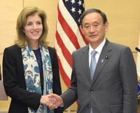 Then Chief Cabinet Secretary Yoshihide Suga, right, shakes hands with then U.S. ambassador to Japan Caroline Kennedy after a joint press conference to announce an agreement for the partial early return of land around the U.S. Futenma Base in Okinawa, at the prime minister's office on Dec. 4, 2015. (Mainichi/Taro Fujii)