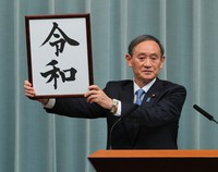 Chief Cabinet Secretary Yoshihide Suga raises a board bearing the new era name