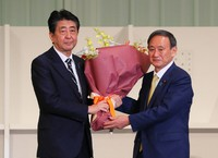 Yoshihide Suga, right, gives a bouquet to outgoing Prime Minister Shinzo Abe after Suga was elected as the new president of the Liberal Democratic Party at a hotel in Tokyo on Sept. 14, 2020. (Mainichi/Naoaki Hasegawa)