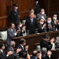 衆院本会議での首相指名選挙で選出され、立ち上がり頭を下げる菅義偉氏(中央)。左中央は安倍晋三前首相=国会内で2020年9月16日午後1時45分、竹内紀臣撮影
