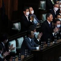 衆院本会議で新首相に指名され一礼する自民党の菅義偉総裁(右奥)と拍手する安倍晋三前首相(左手前)=国会内で2020年9月16日午後1時46分、吉田航太撮影