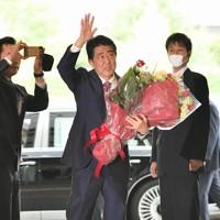 職員らに見送られ花束を手に首相官邸を後にする安倍晋三首相=2020年9月16日午後0時42分、川田雅浩撮影