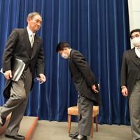 就任後初の記者会見を終え、会見室を出る菅義偉首相(左)。中央は加藤勝信官房長官=首相官邸で2020年9月16日午後9時半、竹内幹撮影