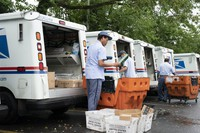 In this July 31, 2020 file photo, letter carriers load mail trucks for deliveries at a U.S. Postal Service facility in McLean, Virginia. (AP Photo/J. Scott Applewhite)