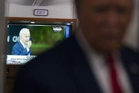 A television screen shows Democratic presidential candidate and former U.S. Vice President Joe Biden holding up a mask, as President Donald Trump talks with reporters on Air Force One while returning to Washington after a campaign rally at Central Wisconsin Airport, on Sept. 17, 2020. (AP Photo/Evan Vucci)