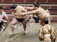 Onosho, left, loses to Chiyotairyu at the Autumn Grand Sumo Tournament on Sept. 18, 2020. (Kyodo)
