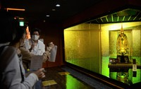 Maruichi Kanko Co. employees prepare for a livestream tour event in front of a replica of Japanese samurai armor using gold leaves at the Hakukokan gold leaf museum, in the central Japan city of Kanazawa, Ishikawa Prefecture, on Sept. 18, 2020. (Mainichi/Hiroyuki Yamanaka)