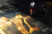 Residents wearing masks to protect from the coronavirus past by reflections of sunlight at a mall district in Beijing on Sept. 18, 2020. (AP Photo/Ng Han Guan)