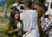 In Sept. 11, 2020 photo, Alena Waqar, a female journalist from local tv channel Geo News, gives live reporting during a rally, in Islamabad, Pakistan. (AP Photo/Anjum Naveed)
