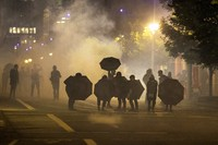 Tear gas fills the air during protests, on Sept. 18, 2020, in Portland, Ore. The protests, which began over the killing of George Floyd, often result frequent clashes between protesters and law enforcement. (AP Photo/Paula Bronstein)