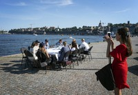 In this Friday, June 26, 2020 file photo employees socially distance due to the coronavirus as they have a drink after work, in Stockholm. (Stina Stjernkvist/TT News Agency via AP, File)